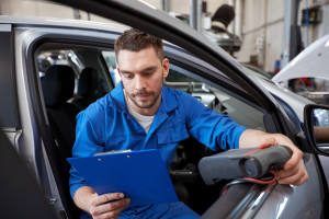 A mechanic uses a diagnostic scanner.