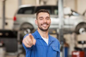 Happy auto mechanic smiles.